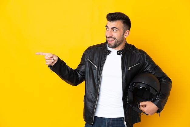 Homem caucasiano com um capacete de motociclista sobre uma parede amarela isolada, apontando o dedo para o lado e apresentando um produto