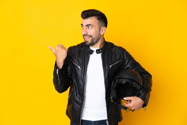Homem caucasiano com um capacete de motociclista sobre uma parede amarela isolada apontando para o lado para apresentar um produto