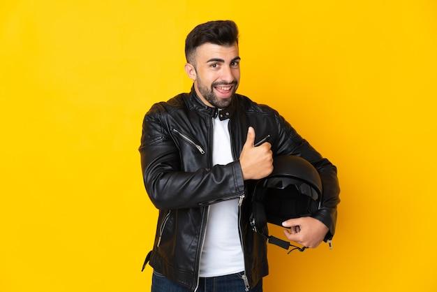Homem caucasiano com um capacete de motociclista sobre uma parede amarela isolada e fazendo um gesto de polegar para cima