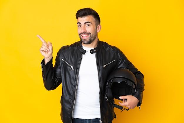 Homem caucasiano com um capacete de motociclista sobre uma parede amarela isolada, mostrando e levantando um dedo em sinal dos melhores