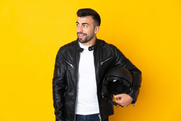 Homem caucasiano com um capacete de motociclista sobre uma parede amarela isolada, olhando para o lado e sorrindo