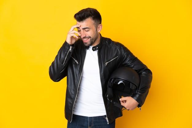 Homem caucasiano com um capacete de motociclista sobre uma parede amarela isolada rindo