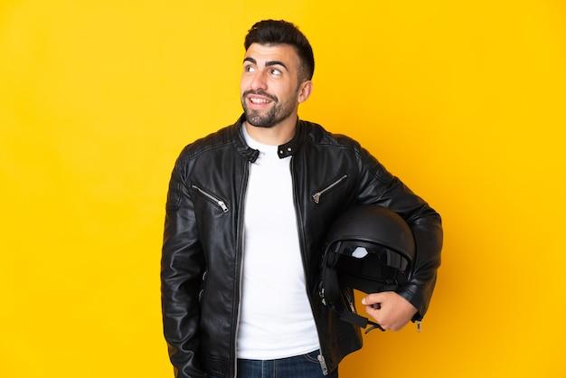 Homem caucasiano com um capacete de motociclista sobre uma parede amarela isolada, tendo uma ideia enquanto olha para cima