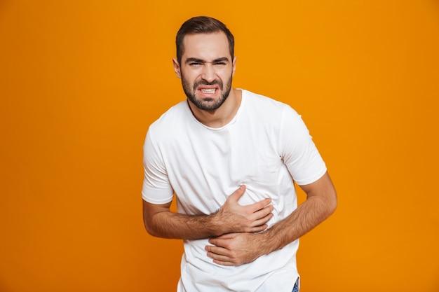 Homem caucasiano com uma camiseta, dobrando-se e tocando a barriga por causa da dor, enquanto, isolado no amarelo