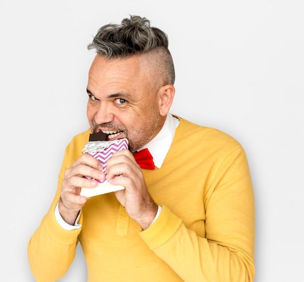 Homem caucasiano comendo chocolate sorriso