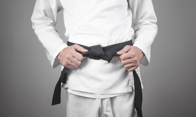 Homem caucasiano, consertando a faixa preta. karatê