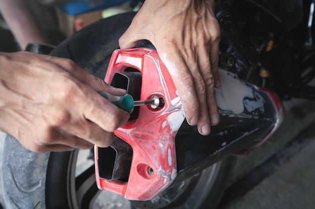 Homem caucasiano consertando sua motocicleta na garagem.
