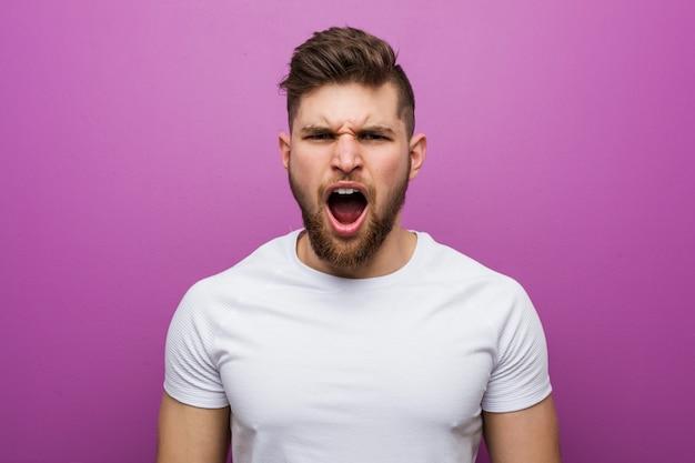 Homem caucasiano considerável novo que grita muito irritado e agressivo.