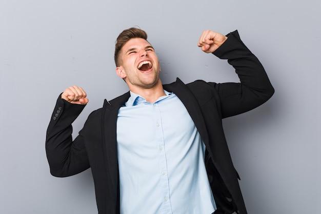 Homem caucasiano considerável novo que levanta o punho após uma vitória, conceito do vencedor.