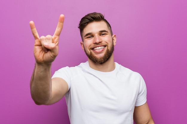 Homem caucasiano considerável novo que mostra um gesto dos chifres como um conceito da revolução.