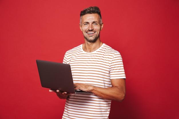 Homem caucasiano de 30 anos em camiseta listrada sorrindo enquanto segura e usa laptop isolado no vermelho