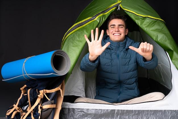 Homem caucasiano de adolescente dentro de uma barraca de acampamento verde isolada na parede preta, contando seis com os dedos