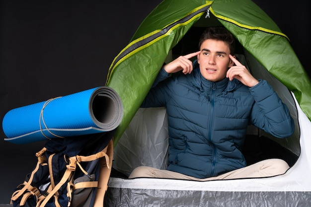 Homem caucasiano de adolescente dentro de uma barraca de acampamento verde isolada no fundo preto tendo dúvidas e pensando