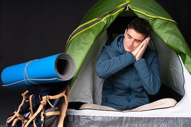 Homem caucasiano de adolescente dentro de uma barraca de acampamento verde isolada no preto