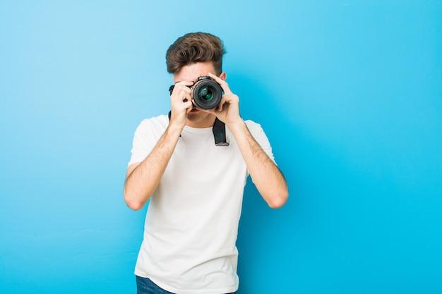 Homem caucasiano de adolescente tirando fotos com uma câmera reflex