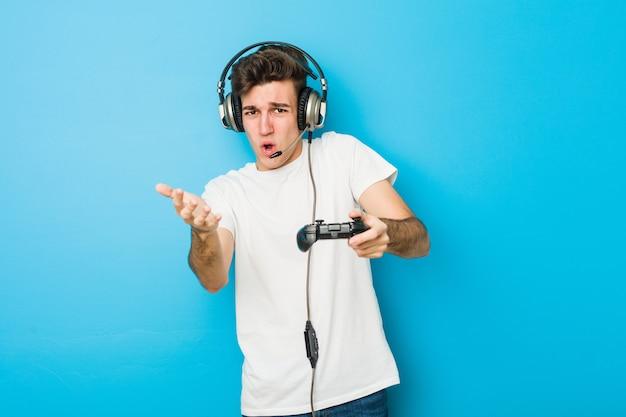 Homem caucasiano de adolescente usando fones de ouvido e controlador de jogo