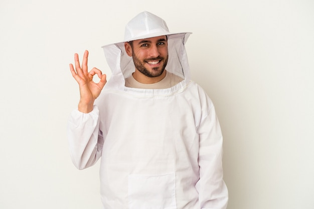 Homem caucasiano de apicultura jovem isolado no fundo branco alegre e confiante, mostrando um gesto ok.