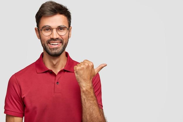 Homem caucasiano de barba alegre com sorriso gentil, vestido com roupa casual, mostra a direção para um lugar agradável, indica com o polegar de lado