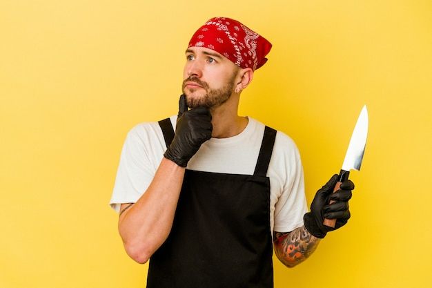 Homem caucasiano de batcher tatuado jovem segurando uma faca isolada em fundo amarelo, olhando de soslaio com expressão duvidosa e cética.