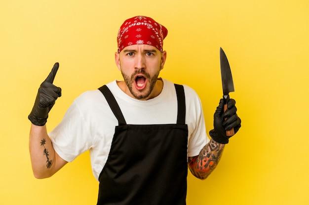 Homem caucasiano de batcher tatuado jovem segurando uma faca isolada em um fundo amarelo, tendo uma ideia, o conceito de inspiração.