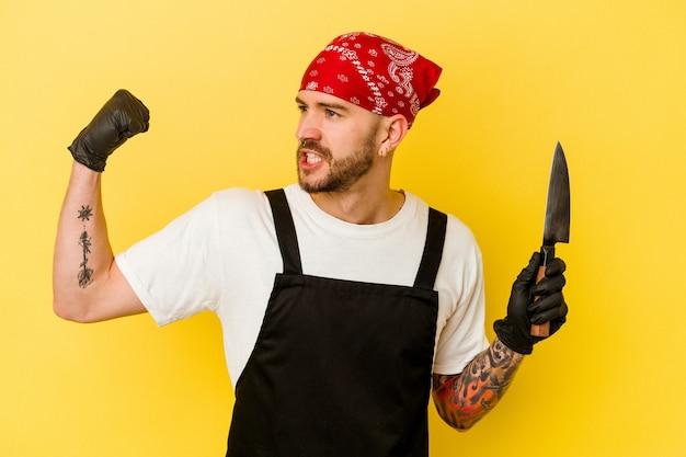 Homem caucasiano de batcher tatuado jovem segurando uma faca isolada no fundo amarelo, levantando o punho após uma vitória, o conceito de vencedor.