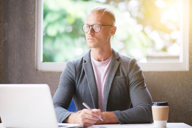 Homem caucasiano de blazer e óculos, sentado na mesa no escritório, segurando a caneta e desviar o olhar