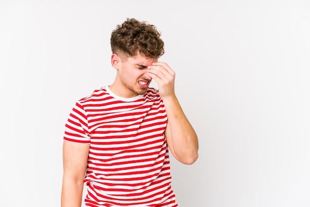 Homem caucasiano de cabelo cacheado loiro jovem isolado tendo uma dor de cabeça, tocando a frente do rosto.