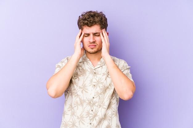 Homem caucasiano de cabelo encaracolado jovem loiro isolado tocando as têmporas e tendo dor de cabeça.
