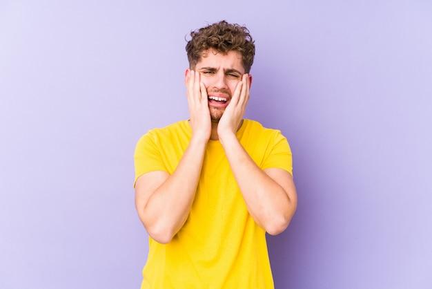 Homem caucasiano de cabelo encaracolado loiro jovem choramingando e chorando desconsolado.