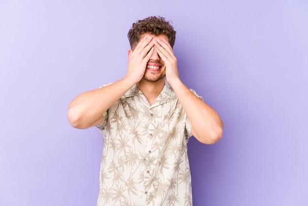 Homem caucasiano de cabelo encaracolado loiro jovem cobre os olhos com as mãos, sorri amplamente esperando por uma surpresa.