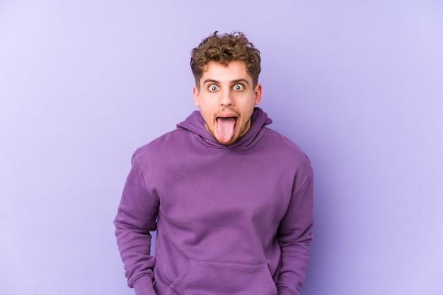 Homem caucasiano de cabelo encaracolado loiro jovem engraçado e amigável saindo da língua.