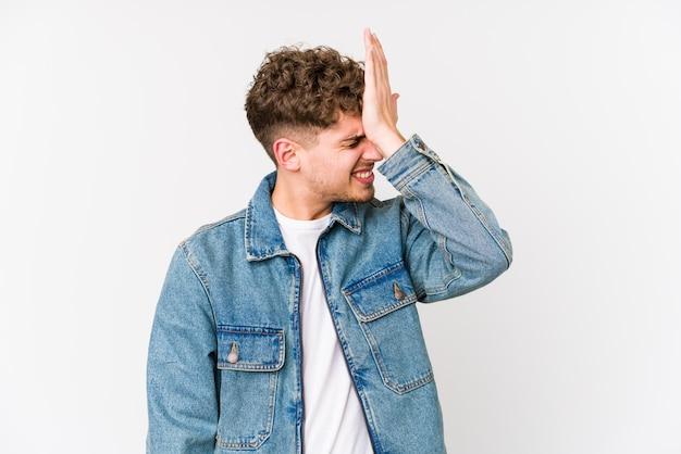 Homem caucasiano de cabelo encaracolado loiro jovem esquecendo algo, batendo na testa com a palma da mão e fechando os olhos.