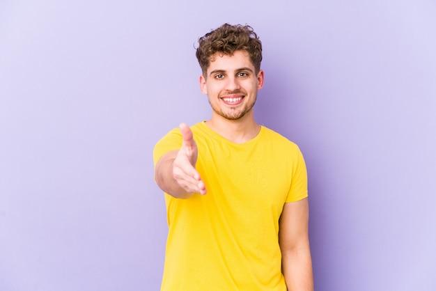 Homem caucasiano de cabelo encaracolado loiro jovem isolado esticando a mão na câmera em gesto de saudação.