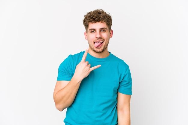 Homem caucasiano de cabelo encaracolado loiro jovem isolado mostrando o gesto do rock com os dedos