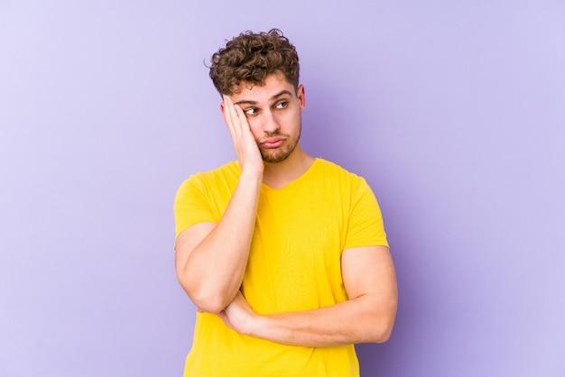 Homem caucasiano de cabelo encaracolado loiro jovem isolado quem está entediado, cansado e precisa de um dia de relaxamento.