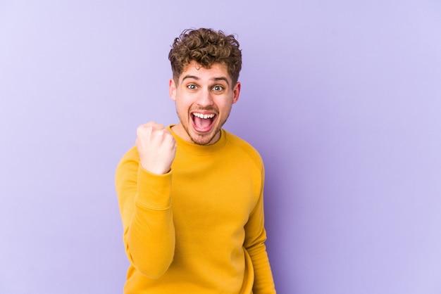 Homem caucasiano de cabelo encaracolado loiro jovem torcendo despreocupado e animado