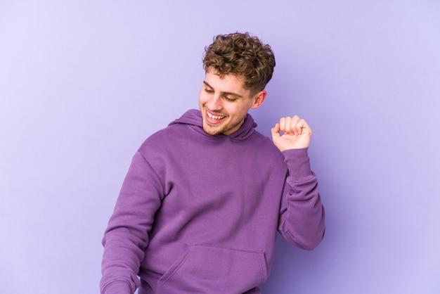Homem caucasiano de cabelo loiro encaracolado jovem dançando e se divertindo.