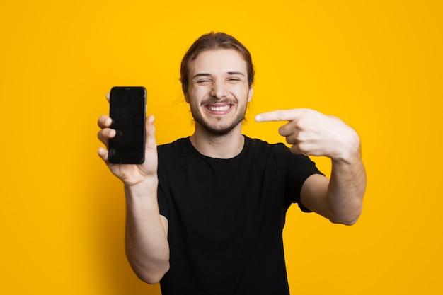 Homem caucasiano de cabelos compridos com barba apontando para o telefone com espaço livre na parede amarela