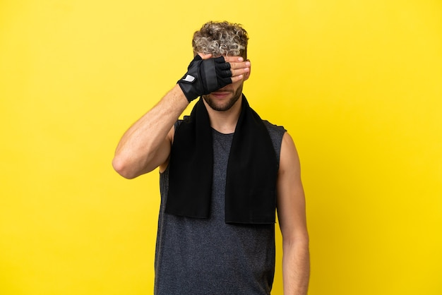 Homem caucasiano de esporte isolado em um fundo amarelo, cobrindo os olhos pelas mãos. não quero ver nada