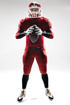 Homem caucasiano de fitness como jogador de futebol americano segurando uma bola no fundo branco