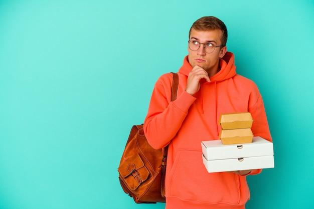 Homem caucasiano de jovem estudante segurando hambúrgueres e pizzas isoladas em azul, olhando de soslaio com expressão duvidosa e cética.