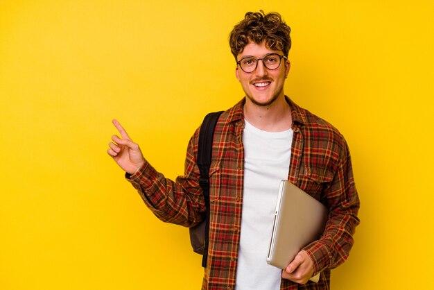 Homem caucasiano de jovem estudante segurando um laptop isolado em um fundo amarelo, sorrindo e apontando de lado, mostrando algo no espaço em branco.