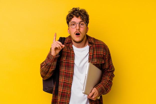 Homem caucasiano de jovem estudante segurando um laptop isolado em um fundo amarelo, tendo uma ideia, o conceito de inspiração.
