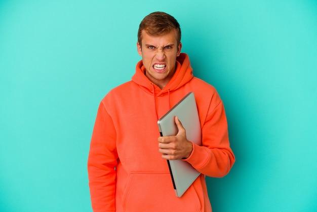 Homem caucasiano de jovem estudante segurando um laptop isolado no azul, gritando muito zangado e agressivo.
