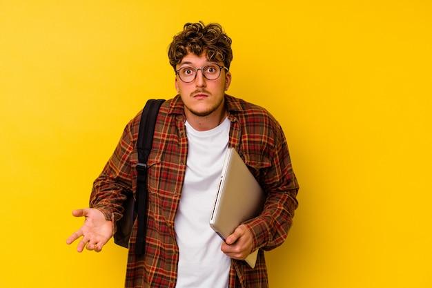 Homem caucasiano de jovem estudante segurando um laptop isolado no fundo amarelo encolhe os ombros e abre os olhos confusos.