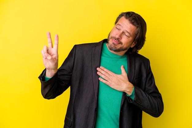 Homem caucasiano de meia-idade em amarelo fazendo um juramento, colocando a mão no peito.