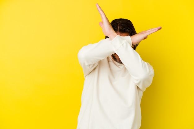 Homem caucasiano de meia-idade em amarelo, mantendo os dois braços cruzados, o conceito de negação.