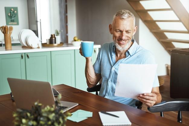 Homem caucasiano de meia idade feliz sentado à mesa com uma xícara de café durante um dia de trabalho remoto em casa