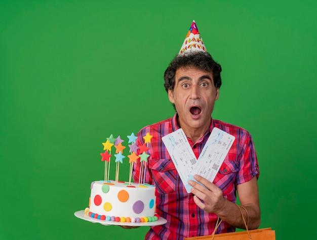 Homem caucasiano de meia-idade, festeiro, impressionado, usando um boné de aniversário, segurando um saco de papel de bolo de aniversário e passagens de avião, olhando para a câmera isolada no fundo verde com espaço de cópia