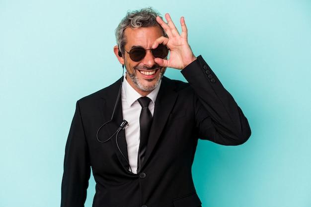 Homem caucasiano de meia-idade guarda-costas isolado sobre fundo azul animado, mantendo o gesto ok no olho.